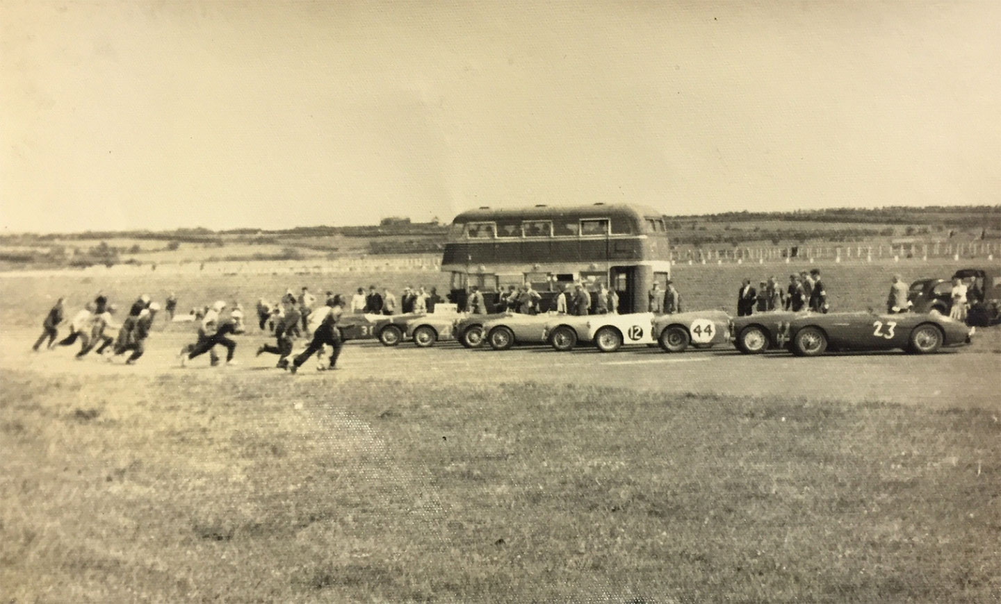 1956 and shows the start of a race for Austin Healeys and Triumph TR2s.